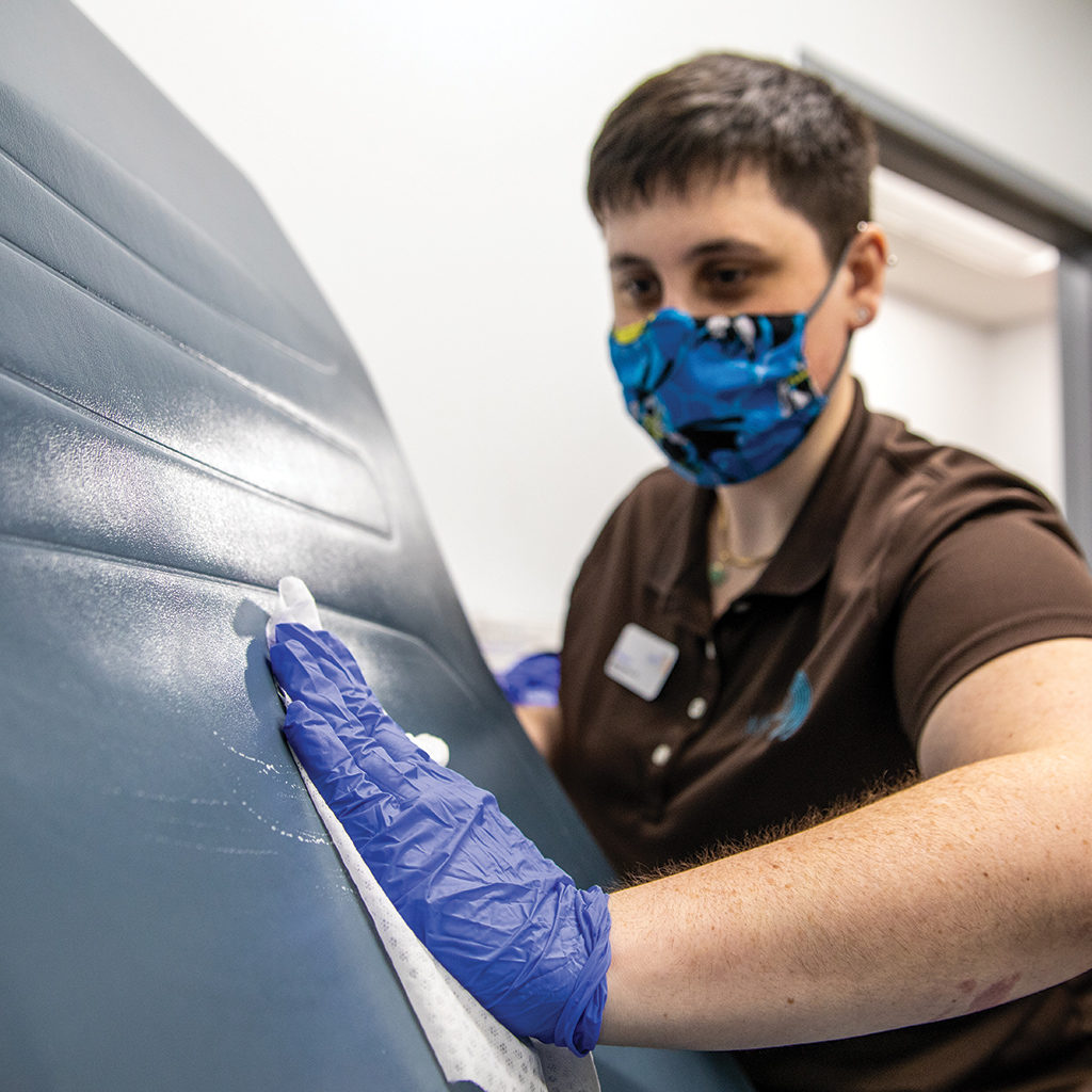 A METRO staff member sanitizes a treatment room between patients while wearing gloves and a mask