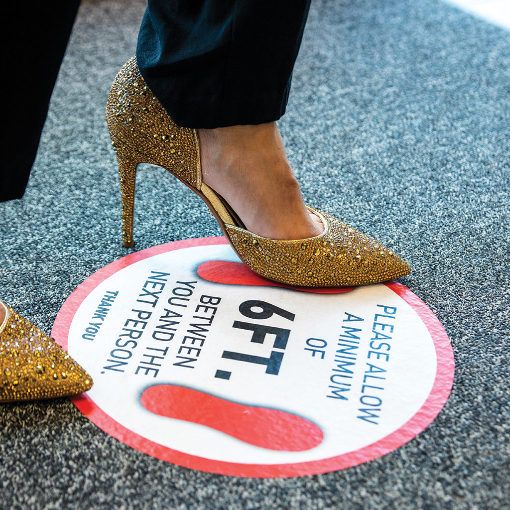 """Someone wearing Glittery golden heels and black pants steps onto the floor sign that reads """"please allow a minimum of 6 ft between you and the next person. thank you"""""""