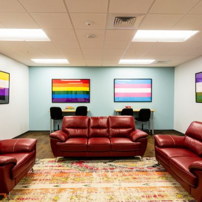 Party room at METRO set up with red couches and Pride flags